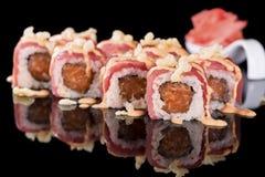 Sushi-Rolle mit Lachsen und Ingwer über schwarzem Hintergrund mit Re Lizenzfreie Stockbilder