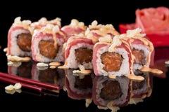 Sushi-Rolle mit Lachsen und Ingwer über schwarzem Hintergrund mit Re Lizenzfreies Stockbild
