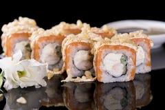 Sushi-Rolle mit Lachsen und Krebsfleisch über schwarzem Hintergrund mit Lizenzfreie Stockfotos