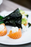Sushi rolled with salmon fish and filadelfia cheese, temaki sushi in the background Royalty Free Stock Photography