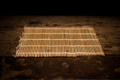 Sushi rolling mat on wood surface Royalty Free Stock Photos