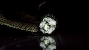 Sushi rolling process with black bamboo makisu, isolated on black background. Hands in black gloves rolling sushi with stock photos