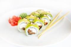 Sushi, rollo y palillo japoneses de los mariscos en una placa blanca Fotografía de archivo