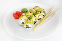 Sushi, rollo y palillo japoneses de los mariscos en una placa blanca Imagen de archivo libre de regalías