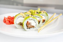 Sushi, rollo y palillo japoneses de los mariscos en una placa blanca fotografía de archivo libre de regalías