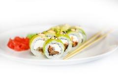 Sushi, rollo y palillo japoneses de los mariscos en una placa blanca Imagenes de archivo