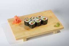 Sushi rolls. A portion of six sushi rolls served on a wooden tray with garnish on the side against a white background Royalty Free Stock Images