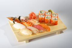Sushi and rolls. Sushi and rolls on the tray on the light background Royalty Free Stock Images
