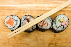 Sushi rolls. Various sushi rolls on cutting board with chopsticks Stock Photos