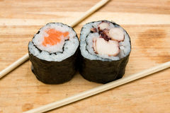 Sushi rolls. Pair of sushi rolls and chopsticks on cutting board Stock Photography