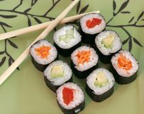 Sushi rolls. With cucumber, carrots, avocado, pepper and rice on decorative plate with chopsticks Stock Photos