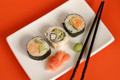 Sushi rolls. Three sushie rolls, ginger, wasabi and sticks in a square plate on orange background Stock Photos