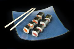 Sushi rolls appetizer on blue plate w/ chopsticks. Sushi Philly rolls appetizer wrapped with rice, tuna, and salmon on square blue plate w/ chopsticks Royalty Free Stock Photos