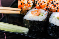 Sushi rolls assortment on black plate and chopsticks. Stock Image