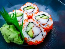 Sushi rolls with avocado and crab, and wasabi paste on a dark background stock photography