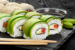 Sushi rolls with avocado, salmon and sesame seeds on slate tray. Royalty Free Stock Images