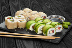 Sushi rolls with avocado, salmon and sesame seeds on slate tray. Stock Photo