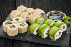 Sushi rolls with avocado, salmon and sesame seeds on slate tray. Stock Photos