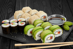 Sushi rolls with avocado, salmon and sesame seeds on slate tray. Royalty Free Stock Photo