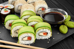 Sushi rolls with avocado, salmon and sesame seeds on slate tray. Royalty Free Stock Photos