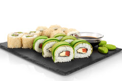 Sushi rolls with avocado, salmon and sesame seeds on slate tray. Stock Images