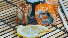 Sushi Rolls on a Bamboo Mat Rotates. Variety of types sushi with red caviar, fish, Philadelphia cheese and chopsticks close-up. Set of delicious Japanese sushi stock video