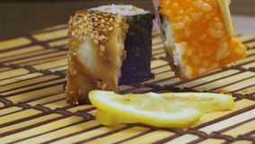 Sushi Rolls on a Bamboo Mat Rotates. Variety of types sushi with red caviar, fish, Philadelphia cheese and chopsticks close-up. Set of delicious Japanese sushi stock footage