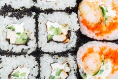 Sushi rolls with black caviar, cucumber and cheese close-up macro shot as a background. Japanese cuisine stock photos