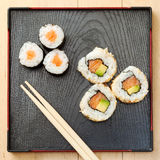 Sushi rolls  on black plate and chopsticks Stock Photos