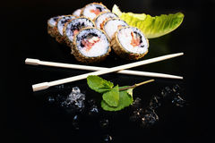 Sushi rolls on a black table with sticks and ice pieces Stock Photography