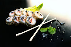 Sushi rolls on a black table with sticks and ice pieces Royalty Free Stock Photos