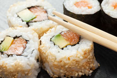 Sushi rolls on black wooden plate Stock Photos