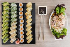 Sushi rolls with ceviche and soy sauce on a wooden table. Salmon fresh shrimp sashimi food rice seafood fish meal japan maki delicacy seaweed traditional tuna royalty free stock images