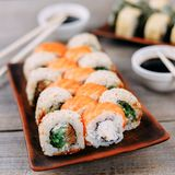 Sushi rolls on clay plates, chopsticks and sauce Stock Images