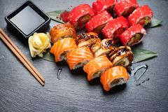 Sushi rolls closeup. Japanese food in restaurant. California sushi roll set with salmon, eel, vegetables and flying fish caviar Stock Photography