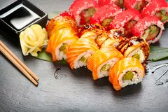 Sushi rolls closeup. Japanese food in restaurant. California sushi roll set with salmon, eel, vegetables and flying fish caviar Stock Image