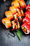 Sushi rolls closeup. Japanese food in restaurant. California sushi roll set with salmon, eel, vegetables and flying fish caviar Stock Images