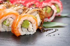 Sushi rolls closeup. Japanese food in restaurant. California sushi roll set with salmon, eel, vegetables and flying fish caviar Stock Photo
