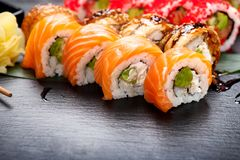 Sushi rolls closeup. Japanese food in restaurant. Roll with salmon, eel, vegetables and flying fish caviar Royalty Free Stock Image