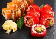 Sushi rolls closeup. Japanese food in restaurant. Roll with salmon, eel, vegetables and flying fish caviar Stock Images