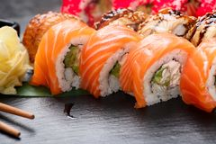 Sushi rolls closeup. Japanese food in restaurant. Roll with salmon, eel, vegetables and flying fish caviar on black slate stock image