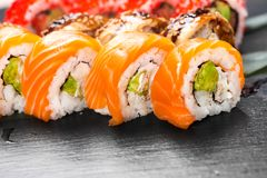 Sushi rolls closeup. Japanese food in restaurant. Roll with salmon, eel, vegetables and flying fish caviar Stock Photos