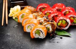 Sushi rolls closeup. Japanese food in restaurant. Roll with salmon, eel, vegetables and flying fish caviar Royalty Free Stock Images