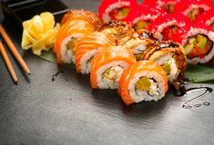 Sushi rolls closeup. Japanese food in restaurant. Roll with salmon, eel, vegetables and flying fish caviar Royalty Free Stock Photo