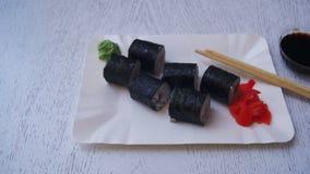Sushi Rolls com Nori em um restaurante japonês em uma tabela de madeira à moda branca Tiro da zorra filme