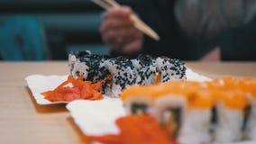Sushi Rolls com salmões em uma placa branca em um restaurante japonês filme
