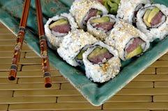 Sushi Rolls con los palillos de la tajada Foto de archivo