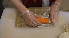 Sushi and rolls. Cooking. Close-up cook`s hands making sushi roll. 4K, h264, Ultra HD stock video footage