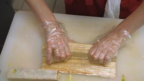 Sushi and rolls. Cooking. Close-up cook`s hands making sushi roll. Add sauce and seasonings, sprinkle rice long sticks. 4K, h264, Ultra HD stock video footage