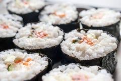 Sushi Rolls de Chumaki com atum, salmões, arroz, pepino, abacate e Nori Seaweed em uma placa fotografia de stock royalty free